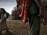Nei pressi di un villaggio un uomo imbraccia un fucile. Là dove le risorse scarseggiano sono frequenti i conflitti tra tribù diverse per il contendersi del territorio.